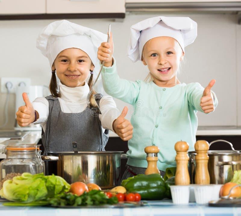 Dos muchachas que preparan verduras y que sonríen dentro fotos de archivo