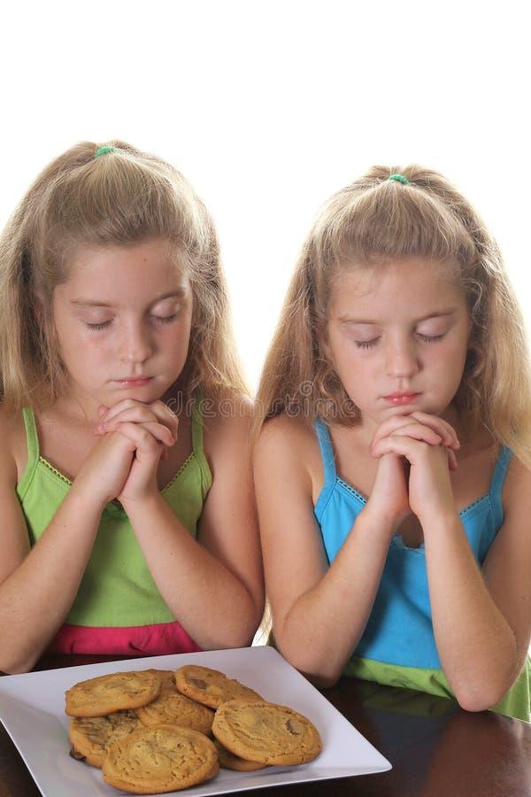 Dos muchachas que ruegan sobre las galletas fotografía de archivo