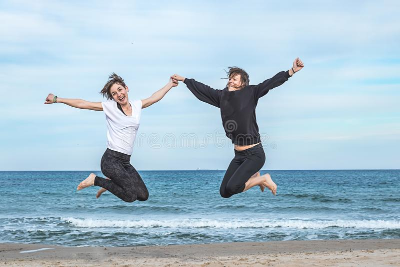 Dos muchachas que saltan en la playa imagen de archivo