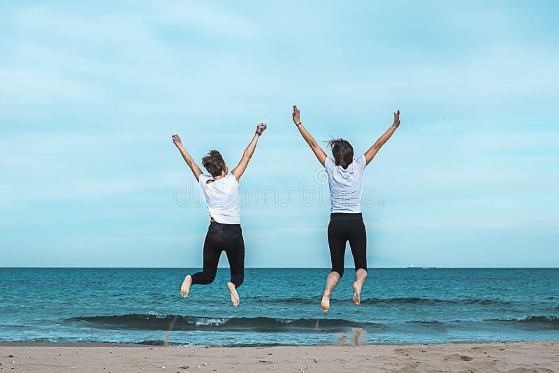 Dos muchachas que saltan en la playa imágenes de archivo libres de regalías