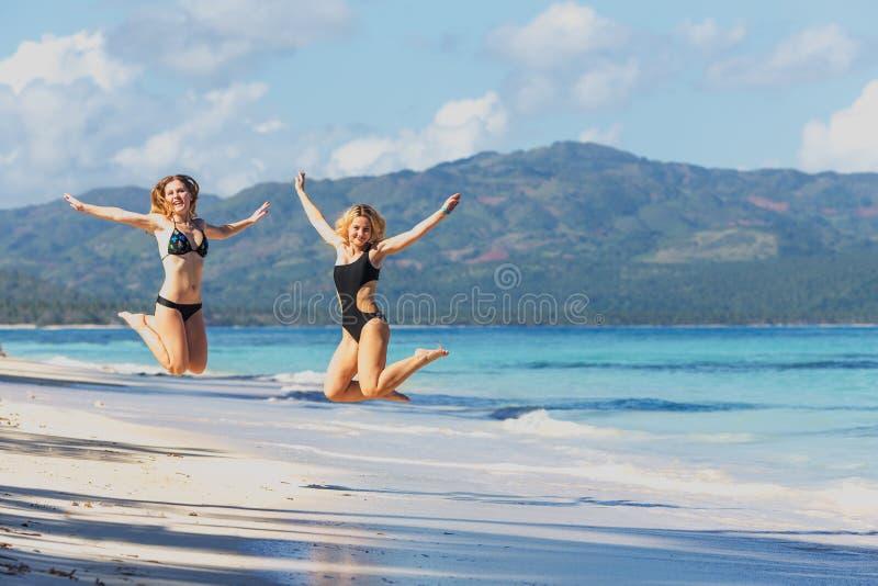 Dos muchachas que saltan en la playa fotografía de archivo libre de regalías