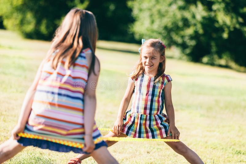 Dos muchachas que se colocan con un elástico envuelto alrededor de sus piernas fotos de archivo libres de regalías
