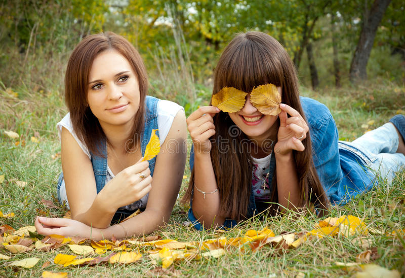 Dos muchachas que se divierten con las hojas amarillas foto de archivo