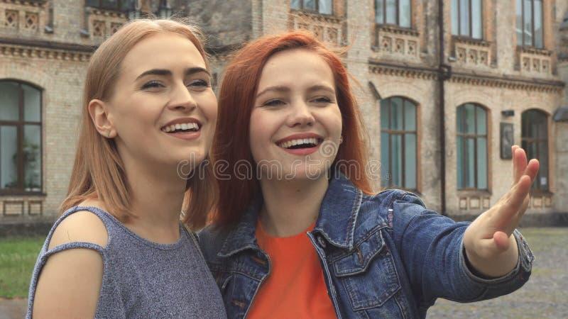 Dos muchachas que se ríen algo delante de ellos imagenes de archivo