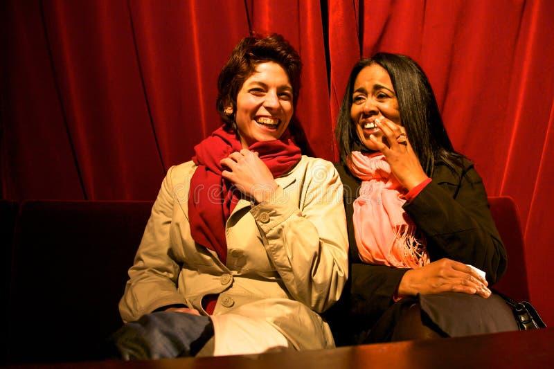 Dos muchachas que se ríen del teatro con una cortina roja en la parte posterior fotos de archivo