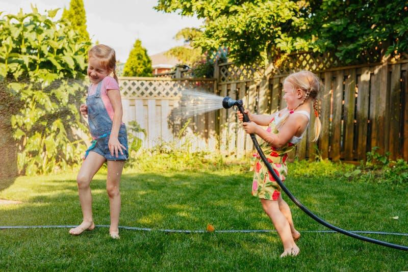 Dos muchachas que se salpican con la casa que cultiva un huerto en patio trasero el día de verano fotografía de archivo