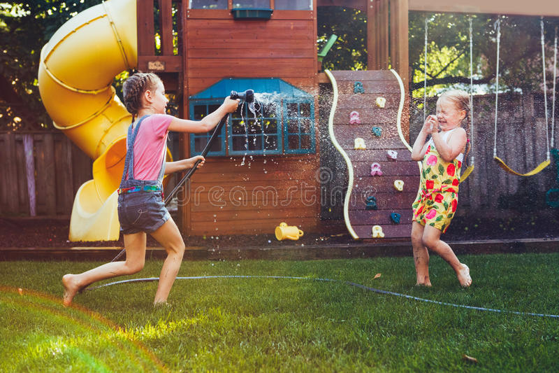 Dos muchachas que se salpican con la casa que cultiva un huerto en patio trasero el día de verano fotos de archivo