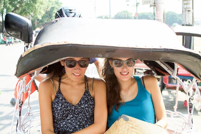 Dos muchachas que se sientan en becak se divierten en Yogyakarta imagenes de archivo