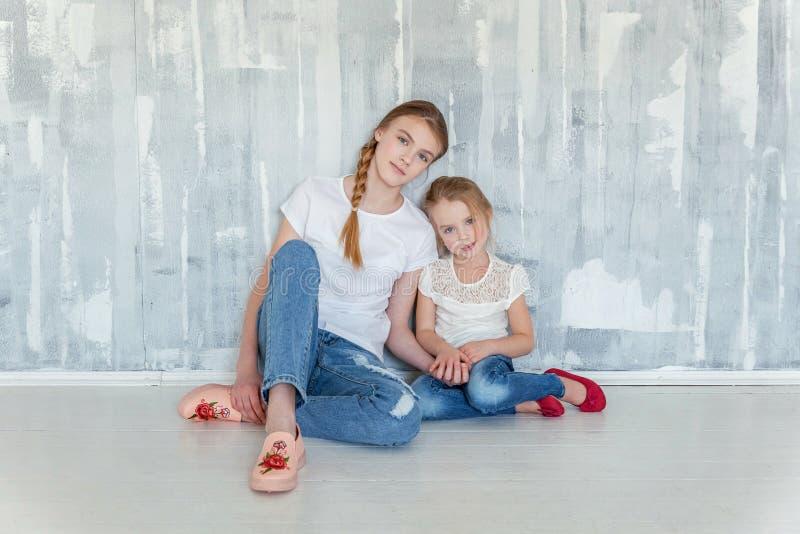 Dos muchachas que se sientan en la pared gris foto de archivo libre de regalías