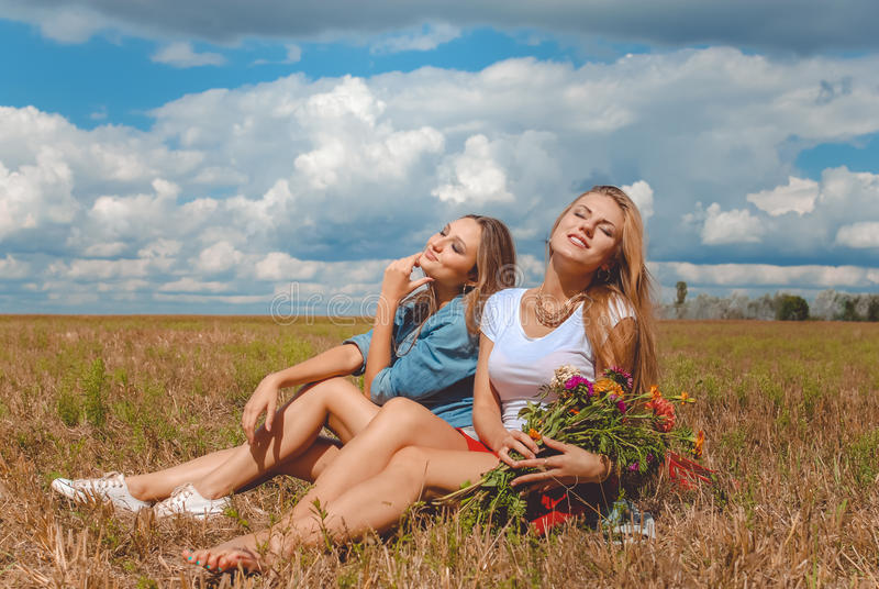 Dos muchachas que se sientan en prado con los wildflowers y imágenes de archivo libres de regalías