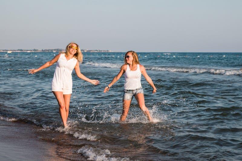 Dos muchachas rubias en la playa cerca del mar fotografía de archivo