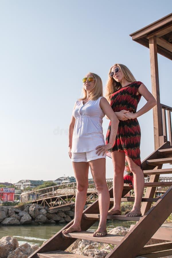 Dos muchachas rubias en la playa cerca del mar foto de archivo