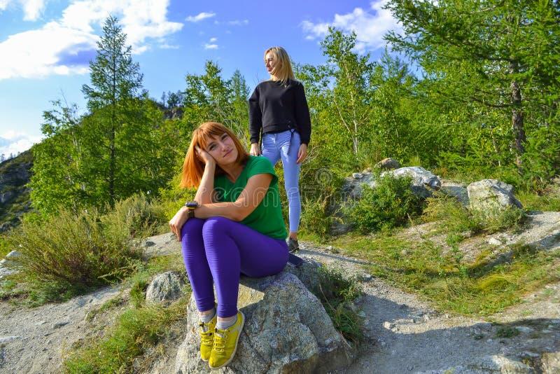 Dos muchachas rubias hermosas jovenes y pelirrojo en una roca en un sunn imagenes de archivo
