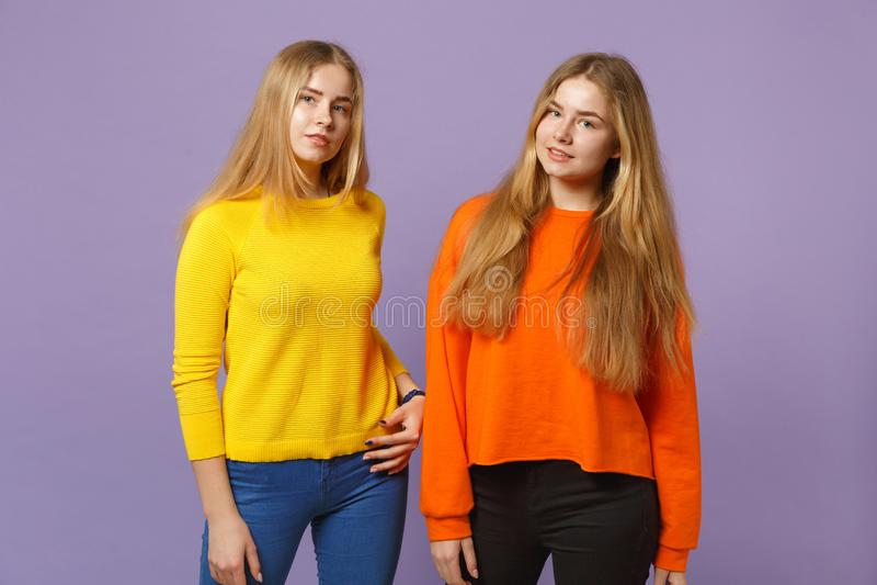 Dos muchachas rubias jovenes de las hermanas de los gemelos en la situación colorida viva de la ropa, mirando la cámara aislada e fotografía de archivo libre de regalías