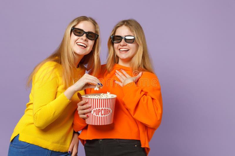 Dos muchachas rubias jovenes de risa de las hermanas de los gemelos en vidrios del imax 3d que miran la película de cine, sostien foto de archivo