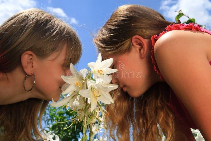 Dos muchachas rubias jovenes detrás del lirio blanco imagen de archivo libre de regalías