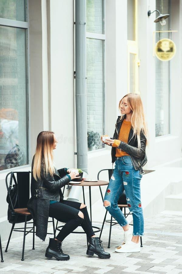 Dos muchachas rubias jovenes hermosas que beben el café y que hablan cerca del café fotografía de archivo libre de regalías