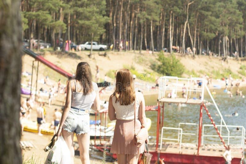 Dos muchachas se colocan en la orilla del lago en un día de verano fotos de archivo