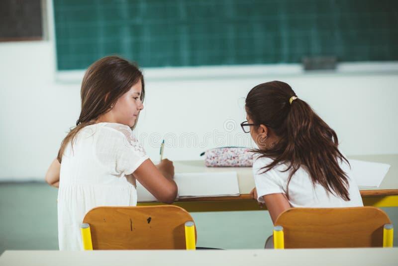 Dos muchachas se sientan en los escritorios de la escuela y miran hacia la pizarra imagen de archivo libre de regalías