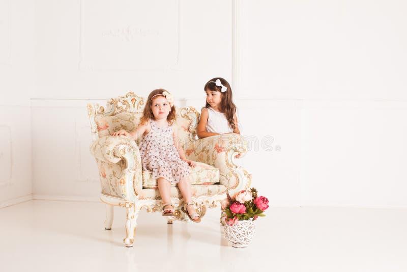 Dos muchachas se sientan en una butaca antigua magnífica imagenes de archivo
