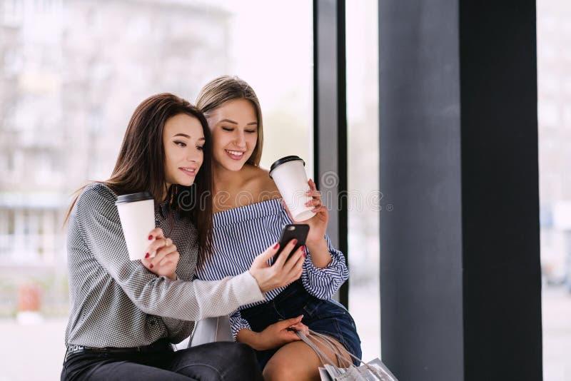 Dos muchachas sientan y beben el café en un centro comercial foto de archivo