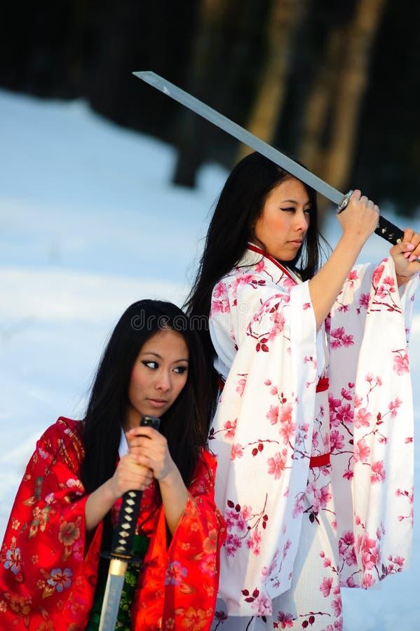 Dos muchachas sobre una espada en manos fotografía de archivo