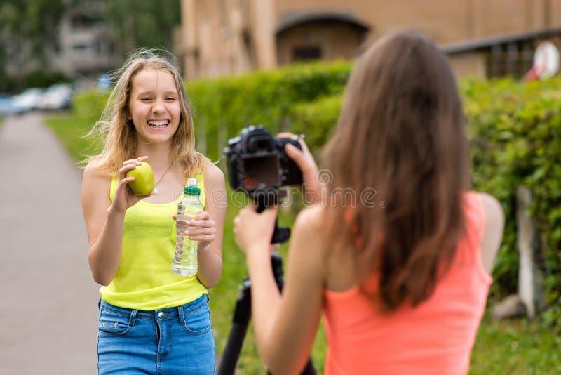 Dos muchachas son novias Verano en naturaleza Escribe el vídeo a la cámara En sus manos sostiene el agua de botella y la manzana  fotografía de archivo libre de regalías