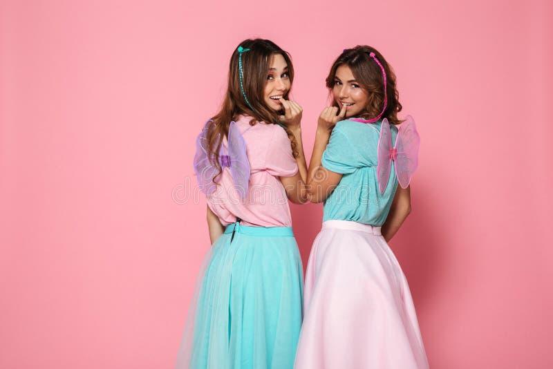 Dos muchachas sonrientes bonitas se vistieron como hadas con las alas fotos de archivo libres de regalías