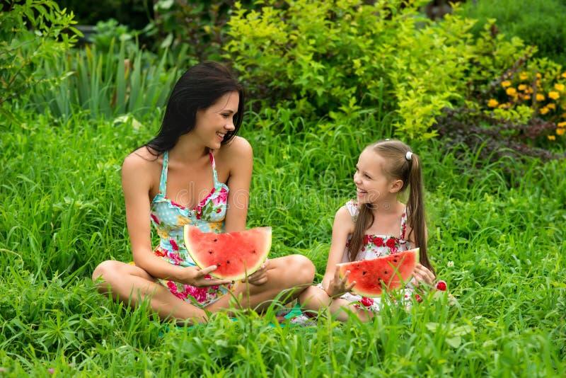 Dos muchachas sonrientes comen la rebanada de sandía al aire libre en la granja imagenes de archivo