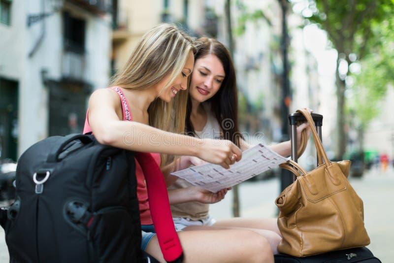 Dos muchachas sonrientes con el mapa imagenes de archivo