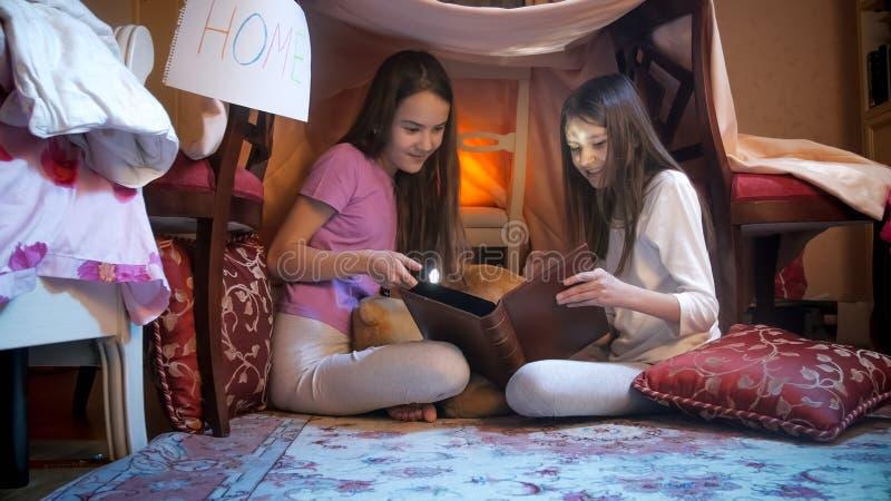 Dos muchachas sonrientes en pijamas que leen el libro grande en tienda selfmade imagen de archivo libre de regalías