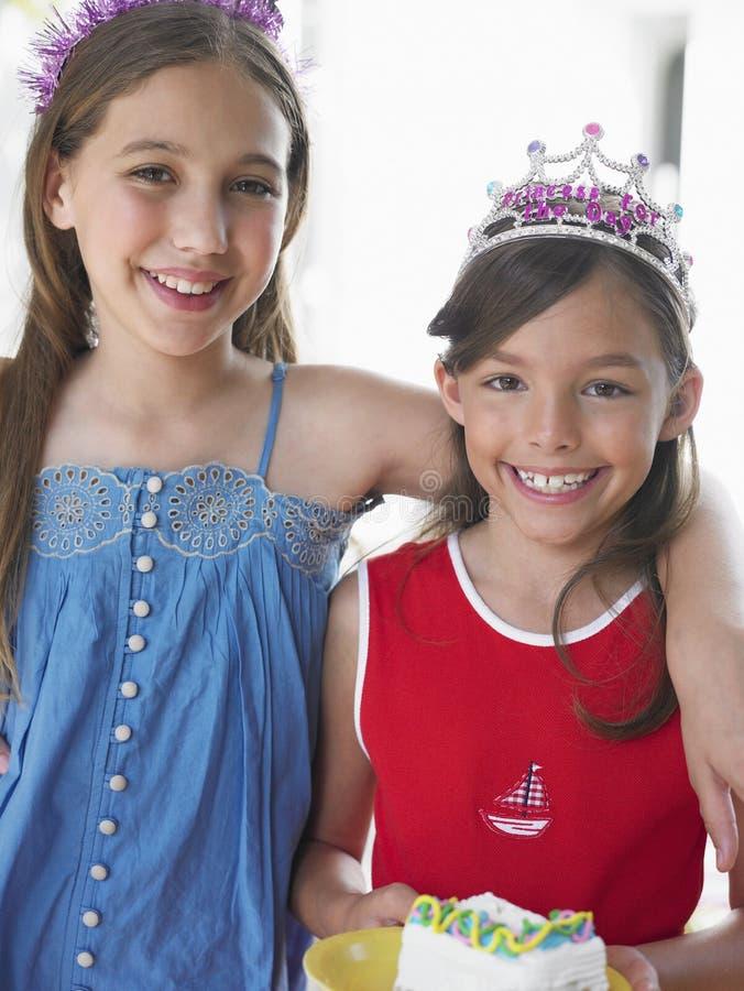 Dos muchachas sonrientes en tiaras imagen de archivo