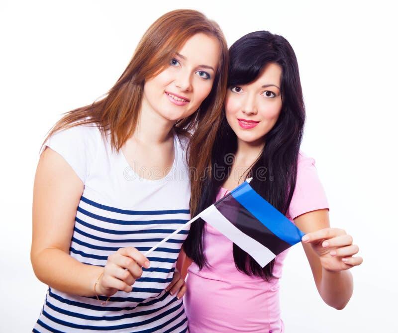 Dos muchachas sonrientes que sostienen la bandera estonia imagen de archivo libre de regalías