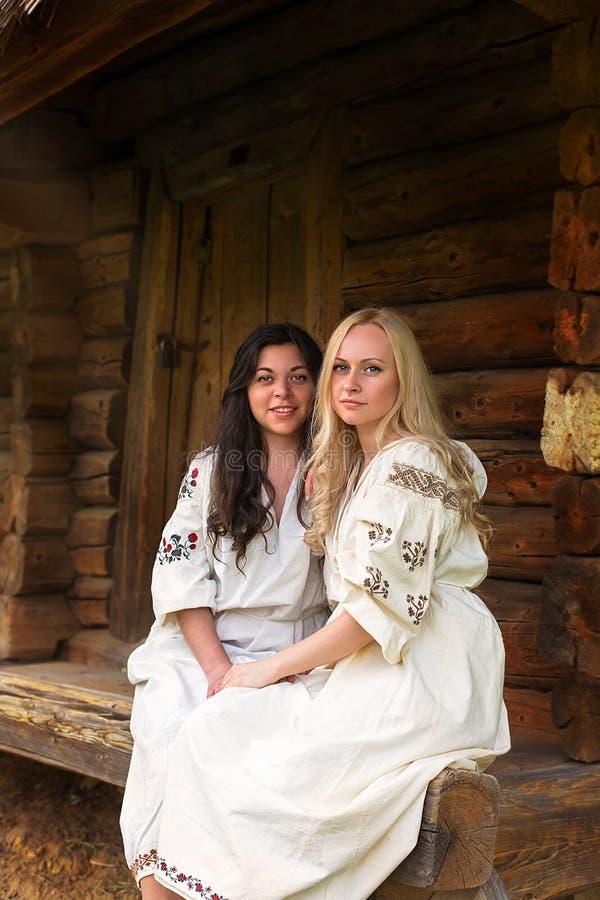 Dos muchachas ucranianas en trajes nacionales en el pórtico fotos de archivo