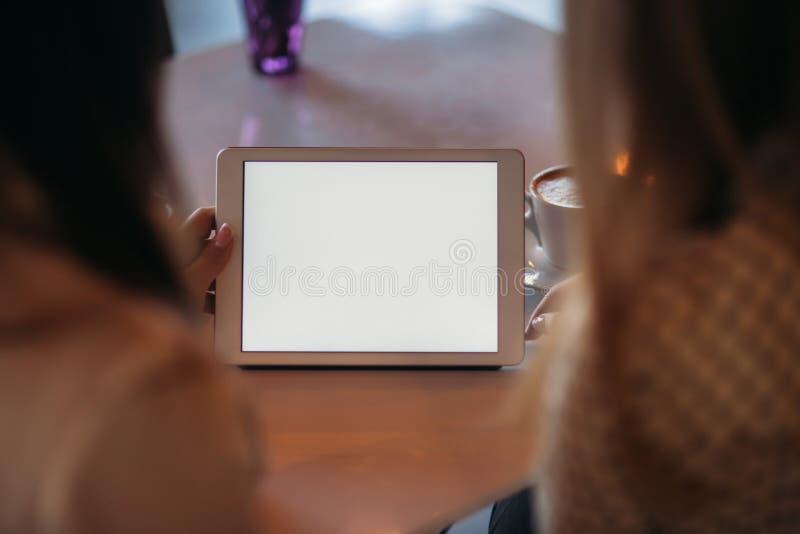 Dos muchachas utilizan una tableta mientras que se sientan en un café y un café de consumición fotos de archivo libres de regalías
