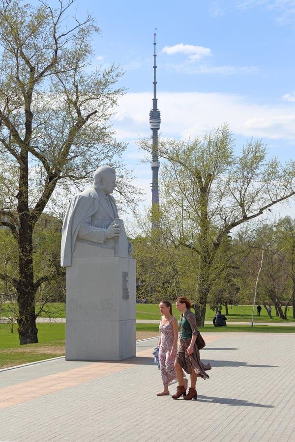 Dos muchachas van cerca del monumento al académico soviético Vladimir Chelomey del diseñador del cohete en Moscú imagen de archivo