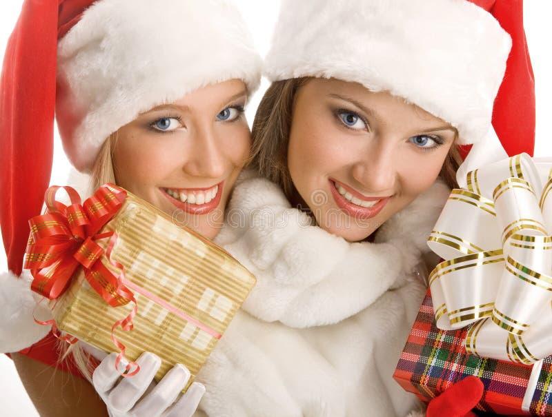 Dos muchachas vestidas como regalos de Santa Claus Happily Hold Boxes With imagen de archivo