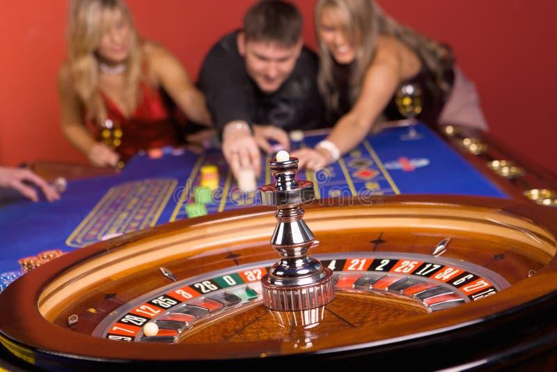Dos muchachas y un hombre en casino fotografía de archivo libre de regalías