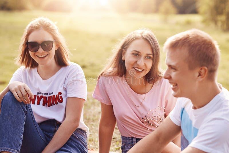 Dos muchachas y un individuo feliz pasa el tiempo libre junto, sientan al aire libre, disfrutan de la naturaleza hermosa, lleva l fotografía de archivo libre de regalías