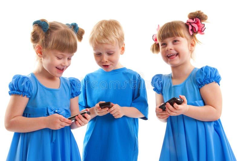 Dos muchachas y un muchacho con sus teléfonos celulares fotos de archivo libres de regalías