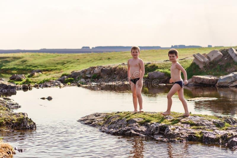 Dos muchachos alegres en el baño de pantalones cortos juegan en un pequeño río en el pueblo fotos de archivo libres de regalías