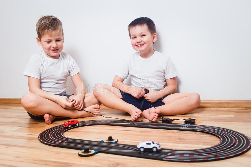 Dos muchachos alegres en las camisetas blancas juegan con los coches y una carretera de los niños foto de archivo