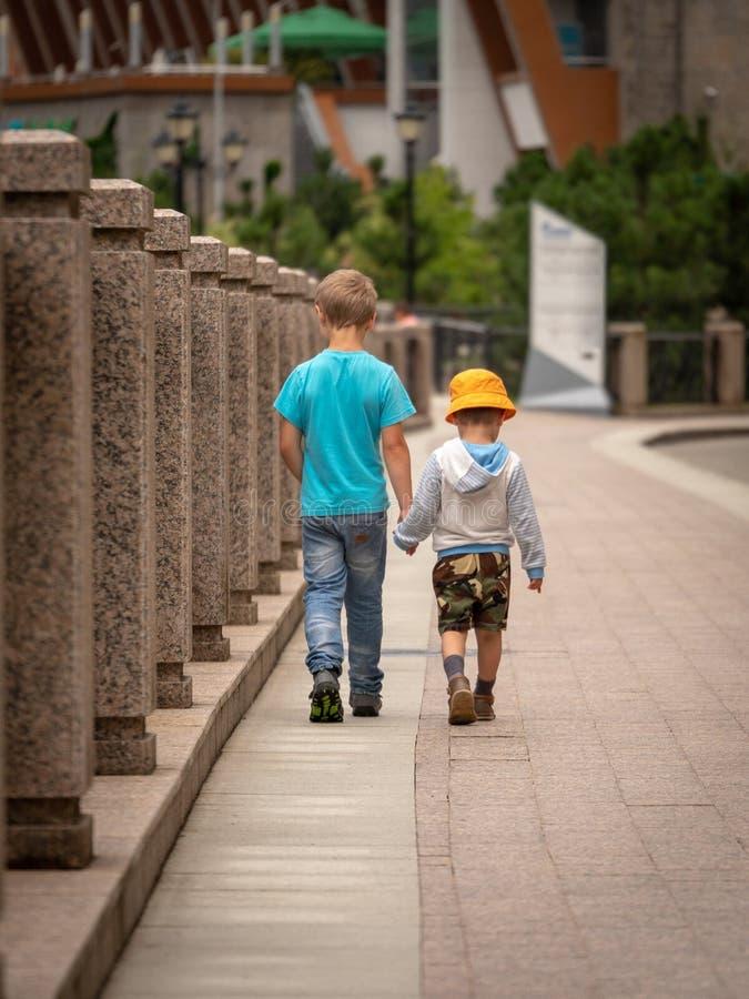 Dos muchachos caminan a lo largo del río de la ciudad fotos de archivo libres de regalías
