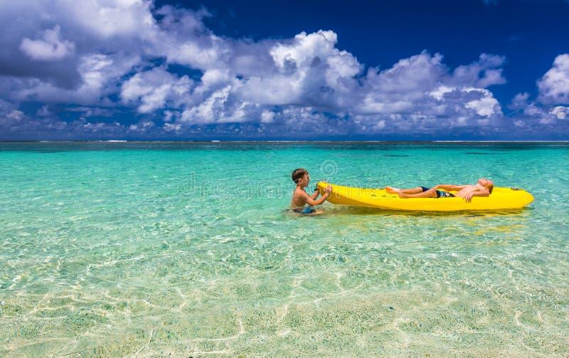 Dos muchachos caucásicos jovenes kayaking en el mar tropical en kaya amarillo imagen de archivo