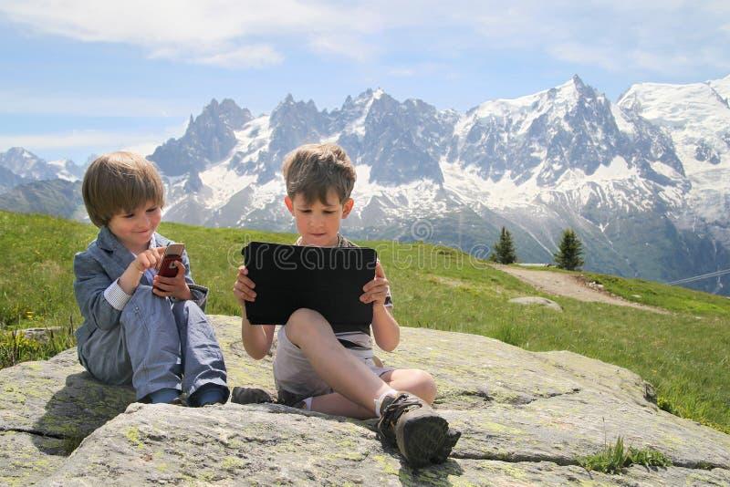 Dos muchachos con PC de la tableta en las montañas imagenes de archivo