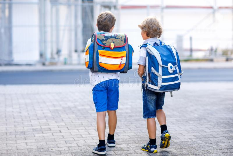 Dos muchachos del niño con la mochila o la taleguilla Alumnos en la manera a la escuela Niños adorables sanos, hermanos y fotos de archivo libres de regalías