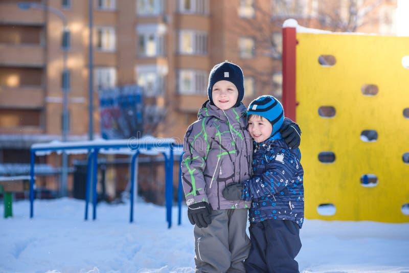Dos muchachos del niño en la ropa colorida que juega al aire libre durante las nevadas Ocio activo con los niños en invierno en d imagen de archivo libre de regalías