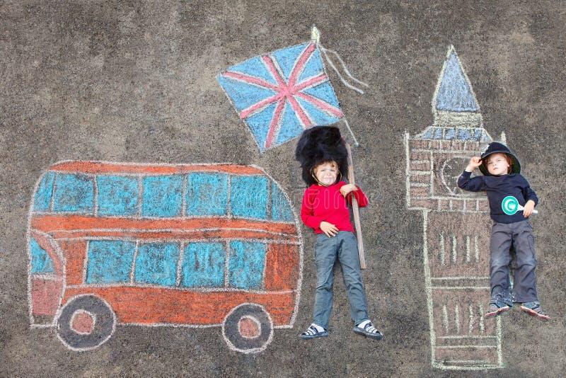 Dos muchachos del niño en policía británico del soldado uniforman con Londres pi imagen de archivo