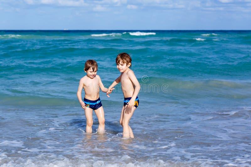 Dos muchachos del niño que corren en la playa del océano Pequeños niños que se divierten fotografía de archivo libre de regalías