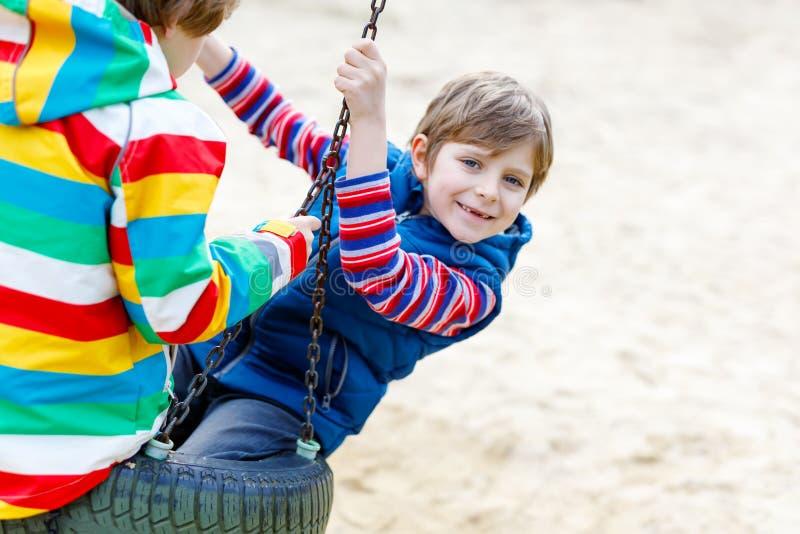 Dos muchachos del niño que se divierten con el oscilación de cadena en patio al aire libre foto de archivo libre de regalías